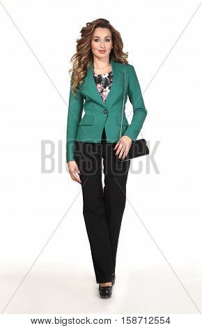 woman with loose hair style in official green jacket and black trousers power suit walking with clutch on white background