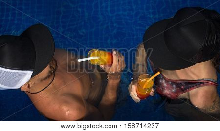 Young couple swimming in swimming pool with cocktails and have a fun at resort.