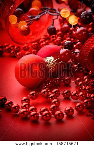 Red Christmas and New Year Decoration isolated on red background. Art design with holiday baubles. Beautiful Christmas Backdrop decorated with ball, holly berry, tinsel, red satin bow