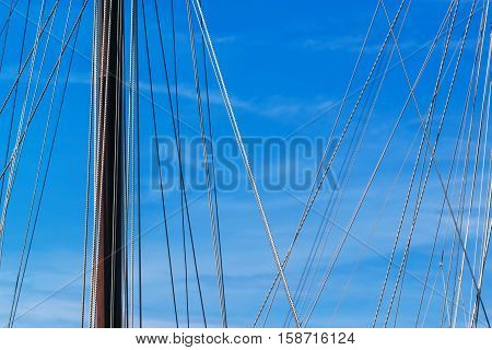 Sailboat mast and ropes in harbor against blue sky summer holiday vacation abstract background