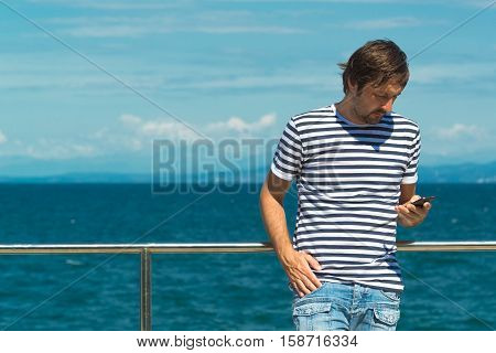 Man in striped sailor shirt sending SMS by the sea. Using mobile phone for communication on summertime beach holiday vacation.