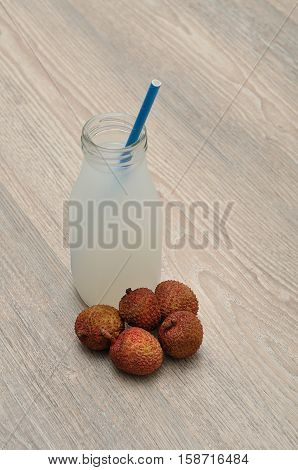 Litchi juice in a glass bottle with a blue straw and fresh litchis .