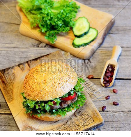 Sandwich with fried bean cutlet, fresh lettuce, red pepper and cucumber. Tasty sandwich and ingredients on old wooden background. Veggie breakfast sandwich idea. Vintage style
