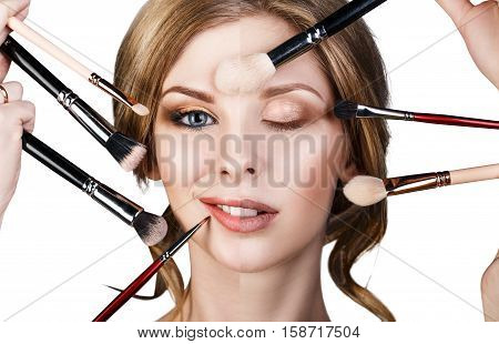 Many hands with cosmetics brushes applying make-up to glamour woman, isolared on white