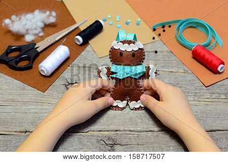 Child holding a felt gingerbread man in his hands. Christmas tree gingerbread man ornament, sewing supplies on old wooden table. Christmas felt crafts for kids. Handmade sewing concept