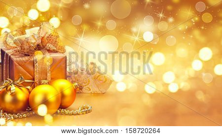 Christmas and New Year Gold color Gift Box and decorations, baubles and tinsel border art design. Winter Holiday celebration art design. Golden Christmas blurred abstract Background