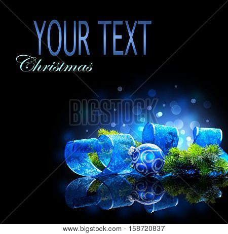 Blue Christmas and New Year Decoration isolated on black background. Border art design with holiday baubles. Beautiful Christmas tree closeup decorated with ball, ribbon, tinsel. Space for your text