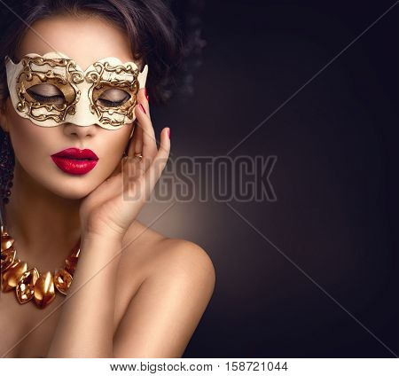 Beauty model woman wearing venetian masquerade carnival mask at party over dark background. Christmas and New Year celebration. Glamour lady with perfect make up and hairstyle