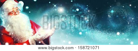 Santa Claus with magic gift in his hands. Portrait of happy Santa Claus making magic at night, Blowing Magic Christmas Stars