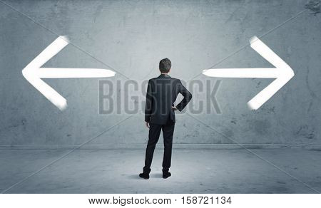 A businessman in doubt, having to shoose between two different choices indicated by arrows pointing in opposite direction concept