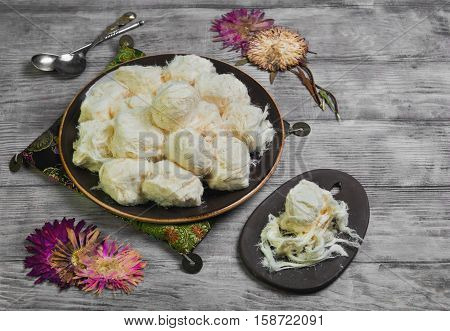 Turkish sweetness of sugar halvah pishmanie. Cloth for Turkish sweets decorative dried flowers. Portion Turkish sweets halva pishmanie on the board. Light white wooden background.