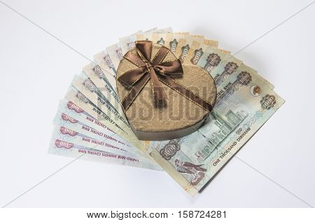 A heart shaped gift box on UAE Dirham currency notes.