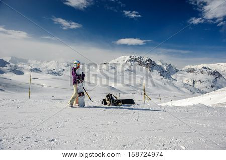 Young woman with snowboard in ski goggles outdoors with French Alps covered with snow at background. Val-d'Isere, France