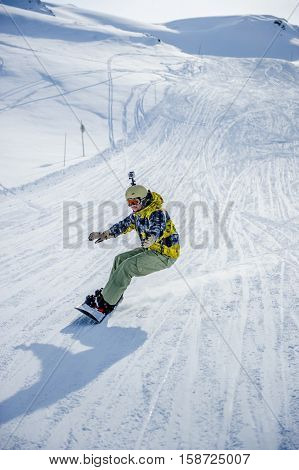 Snowboarder riding at French Alps mountain slopes. Val-d'Isere, France