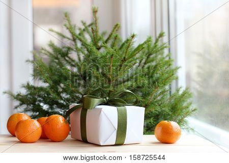 Holiday gift with green bow and mandarin orange fruit on the table under a green tree on a background of a window at sunset / evening before Christmas