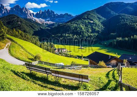 Picturesque Val di Funes. Sunny autumn day in Dolomites, Tirol. Rocky peaks and forested mountains surrounded by green Alpine meadows
