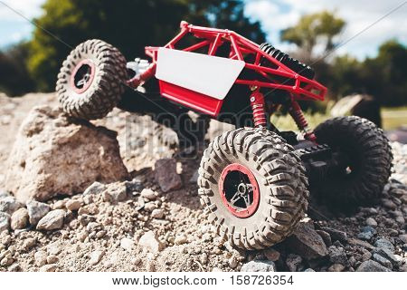 Toy crawler overcoming rock close-up. Rc offroad car riding rocky landscape. Buggy, rally, leisure, entertainment concept