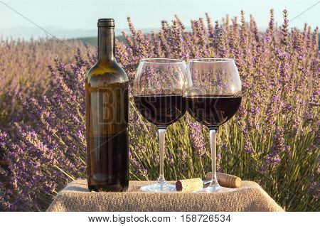 A photo of an open bottle and two glasses of red wine in a lavender field. The glasses are on a crate with a burlap texture, retro corkscrew and a cork
