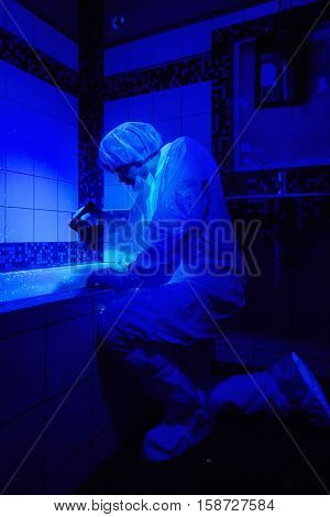 Criminologist at work under UV light in bathroom