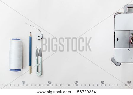 Tailor supplies frame, free space on white background. Top view on sewing machine platform with thread, scissors and pencil on it. Cope space for text. Garment industry backdrop