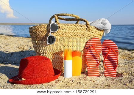 Beach bag, sandals, hat, sunscreen cream and sunglasses on sea coast