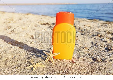 Sunscreen cream and starfish on sea coast