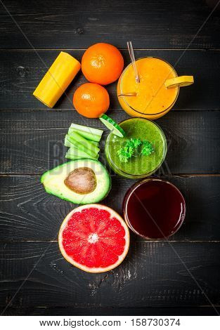 Green, yellow and red smoothies, juices, beverages, drinks variety with fresh fruits and vegetables on black wooden background, top view