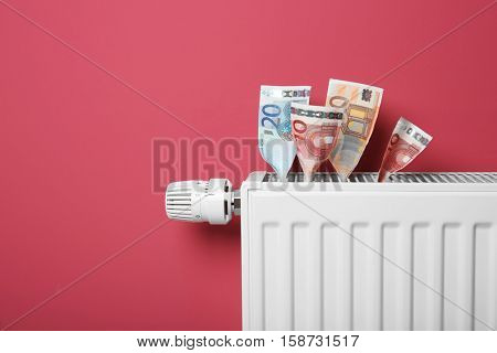 Savings concept. Money and heating radiator with temperature regulator on pink background