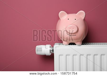 Piggy bank on heating radiator with temperature regulator on pink background, closeup