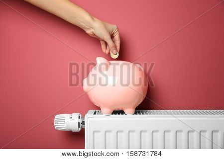 Savings concept. Female hand putting coin into piggy bank which standing on heating radiator with temperature regulator on pink background