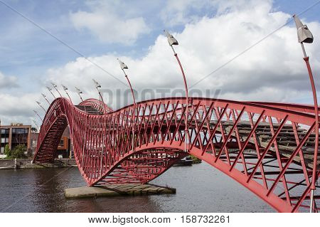 Red sinuous pedestrian bridge in Amsterdam over the river in the day with building as background