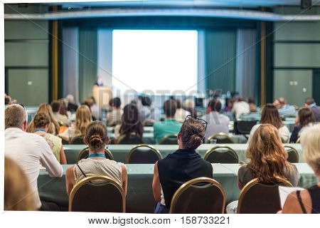 Business and entrepreneurship symposium. Speaker giving a talk at business meeting. Audience in the conference hall. Rear view of unrecognized participant in audience.
