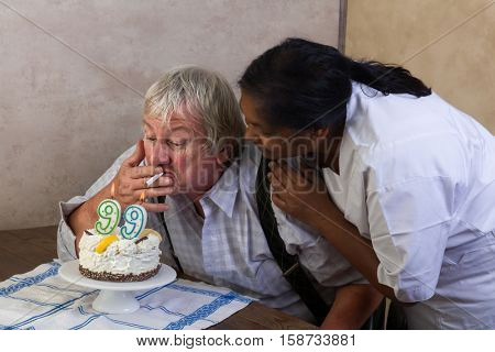 Naughty old pensioner lighting his cigarette on his birthday cake