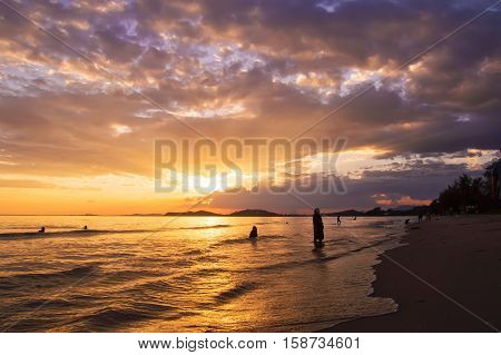 Silhouette of people playing on the beach at sunset