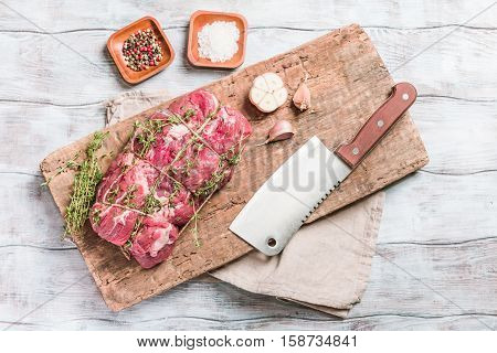 Raw roastbeef meat cut with hyme and garlic and knife on cutting board over old  wooden background, top view