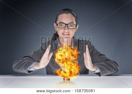 Businesswoman holding burning american dollar sign