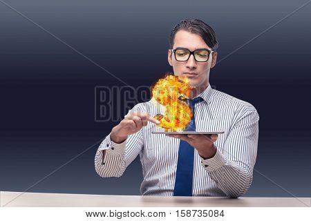Businessman holding burning american dollar sign