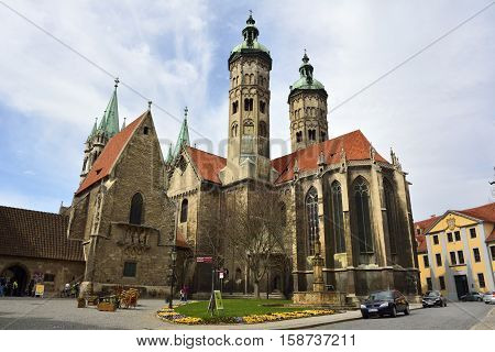 Naumburg, Germany - April 13, 2016. Cathedral of Sts Peter and Paul Dom in Naumburg, with surrounding buildings, cars and people. The church is a masterpiece of medieval architecture.