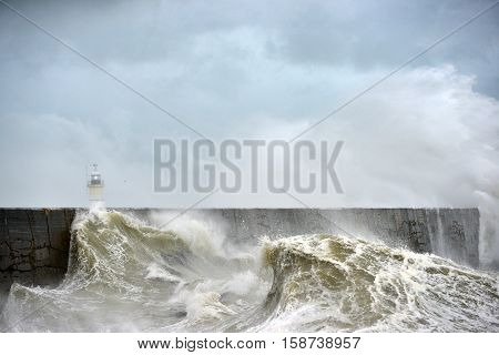 Large waves crashing over a breakwater during winter storms