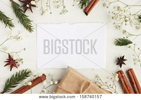 Empty congratulation note framed natural wintertime decor elements. Green pine twigs, cinnamon sticks, craft gift box, white background.