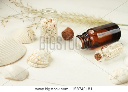 Tropical spa, seaside fragrances. Essential oil, sea shells, sand in decorative bottles. Light, soft focus.