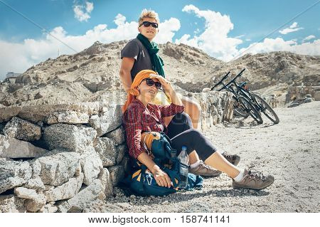 Two bicycle travelers rest on mountain road