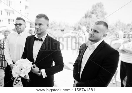 Groom With Wedding Bouquet Of White Orchids On Hand With Groomsman Waiting For Bride. Black And Whit