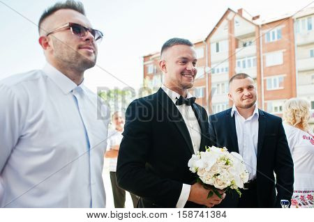 Groom With Wedding Bouquet Of White Orchids On Hand With Groomsman Waiting For Bride.