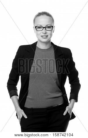 Black and white portrait of beautiful smart young businesswoman in business attire wearin black eyeglasses, standing with arms in pockets against white background.