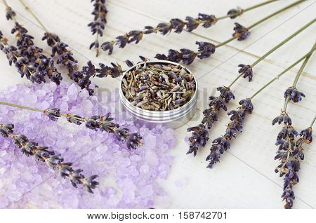 Lavender dried flowers in sample jar and purple herbal sea salt grains. Natural skincare.