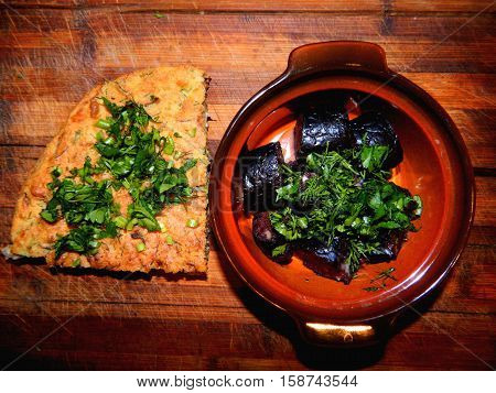 Ukrainian sausage is homemade superalloy in a pot on a wooden chopping board with  herbs parsley and dill with chopped onions, a piece of cake from Millet