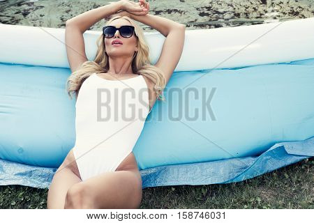 blonde woman relaxing beside a dirty wading pool