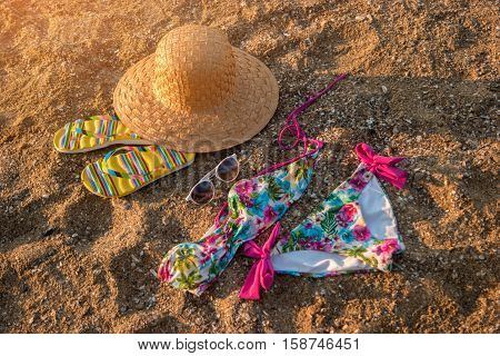 Hat and flip flops. Colorful swimsuit on sand. Be in style of summer. Get away from city bustle.