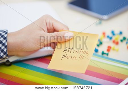Human hand holding adhesive note with Attention please text